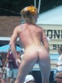 Naked strippers showing off on an outdoor stage