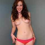 Cute redhead Ruby strips out of her little pink outfit and rubs her wet tight pussy